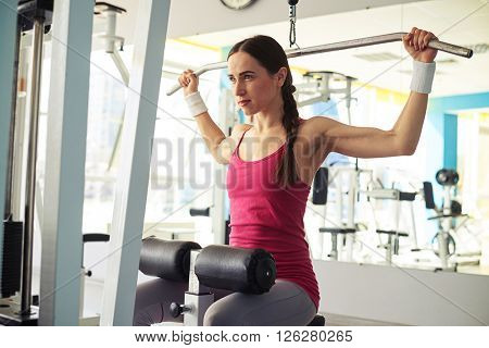 Young Caucasian girl is working out pull-down machine in gym