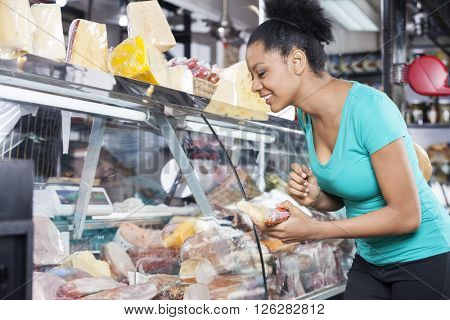 Customer Choosing Product From Cabinet At Store