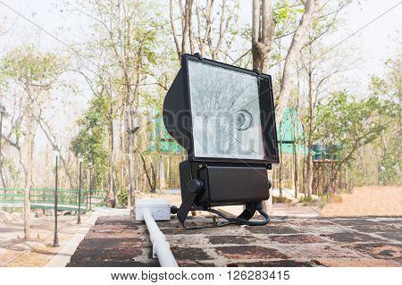 Big black spotlight or footlight set up at outdoor park