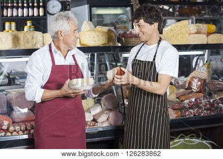 Salesmen Holding Cheese While Looking At Each Other