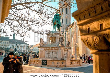 BUDAPEST - FEBRUARY 14, 2015: Couple tourists look pictures on the smart phone on the crowded with tourists Fisherman's Bastion with Matthias church and monument on the background