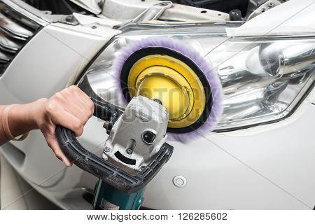 Car detailing series : Worker polishing white car headlights