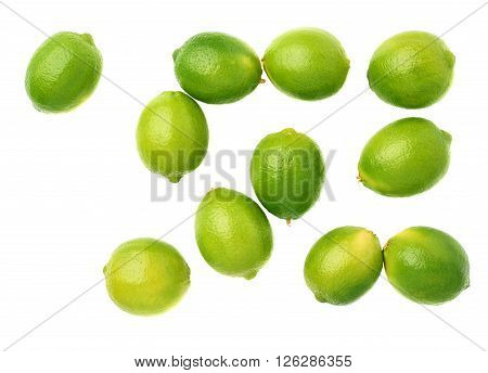 Surface covered with multiple ripe limes, composition isolated over the white background, top view