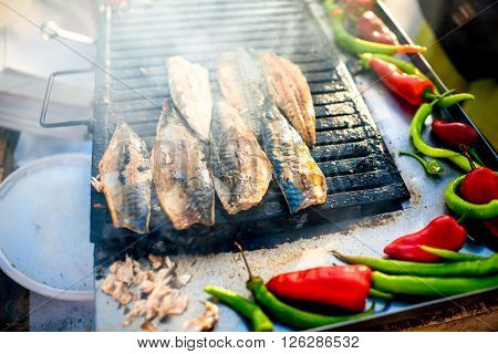 ISTANBUL - MAY 28, 2015: Fish frying on the grill for Balik ekmek sandwich. Balik ekmek is famous turkish street food sandwich made with fish and vegetables