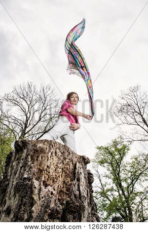 Young joyful woman is posing on the tree stump with waving scarf. Beauty fashion and nature.