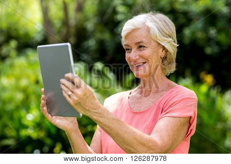 Smiling senior woman with tablet at yard