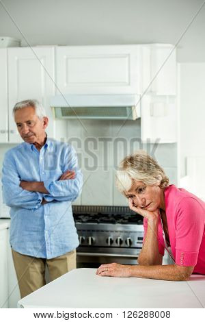 Troubled senior couple after argument while standing in kitchen