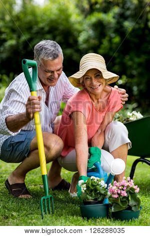 Smiling senior couple with gardening equipment enjoying at yard