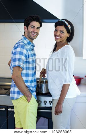 Portrait of young couple cooking food together in kitchen at home