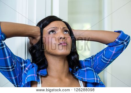Tensed woman with hand on head at home