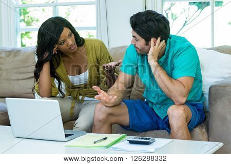 Worried young couple with laptop discussing on bills at home