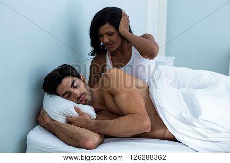 Woman ignoring while man snoring on bed in bedroom