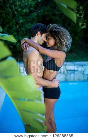 Young couple standing face to face near swimming pool