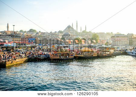 ISTANBUL - MAY 28, 2015: Golden Horn coast and near Galata bridge with popular turkish buffet on boats with fish sandwiches. This place is very famous with lots of restaurants and street foods.