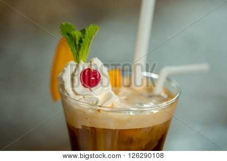 Coffee with cream and ice cream decorated with mint leaf cherry and orange slice