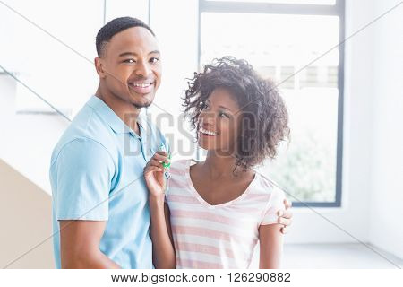 Young couple showing their house key at home