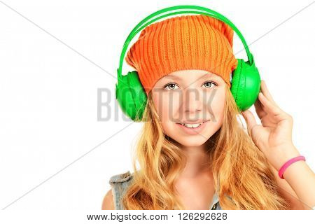 Pretty teenager girl enjoys the music in headphones. Studio shot. Isolated over white. Copy space.