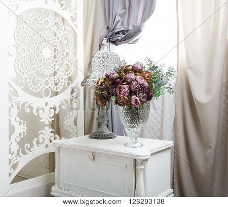 shabby chic room interior. Wedding decor, room decorated for shabby chic rustic wedding, with bedside table, folding screen or room divider with white tracery and rose bouquets. High key, closeup
