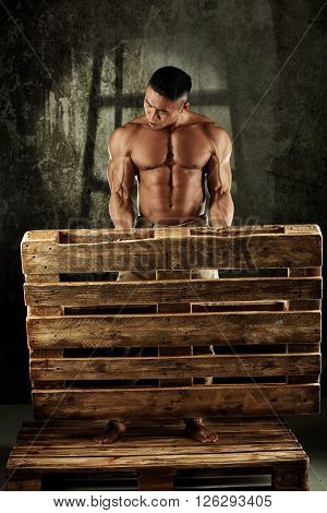 Asian male bodybuilder posing with pallet, bare upper body.