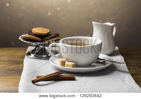 A set of tea cups with saucer and milk jug on light grey napkin