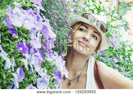 Young caucasian woman posing with beautiful violet flowers in the city park. Schwabach Germany.