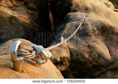 Iron Twisted Rope Streched Between Rocks In Climbers Patch.  Rope Fixed In Block By Screws Snap Hook
