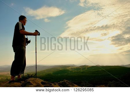 Tourist With Camera On Neck And Poles In Hands On Peak Of Rock. Dreamy Landscape Bellow  In A Beauti