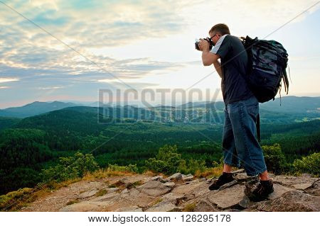 Photographer With Big Mirror Camera On Neck And Backpack Stay On Peak Of Rock. Hilly Landscape, Fres