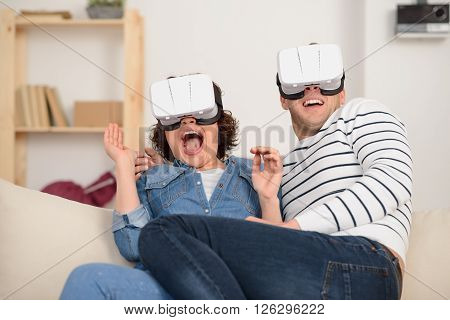 Overwhelmed with emotions. Cheerful thrilled positive loving couple sitting on the couch and using virtual reality device while resting together