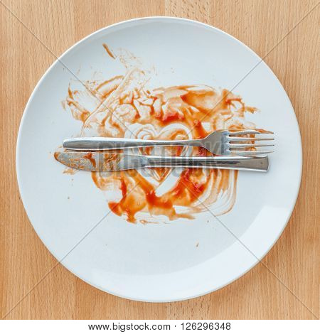 Top view of empty plate tomato sauce smeared on finished plate. Concept of tasty and meaning excellent meal.
