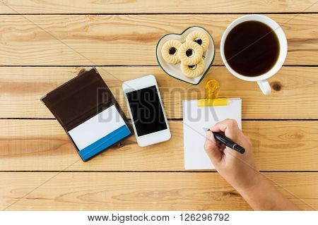 Top View Hand With Pen, Writing Down On Blank Paper Note ,cellphone Coffee And Cookie On Wood Table