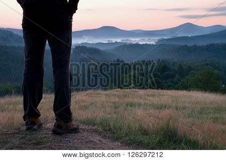 Man Hiker Legs In Tourist Boots Stand On Hill In The Meadow. Sunrise Above Hills.