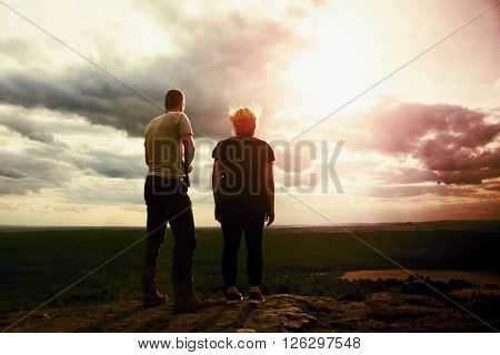 Couple Enjoying Marvellous Moments During Sunset . Young Pair Of Hikers On The Peak Of Rock Watch Ov