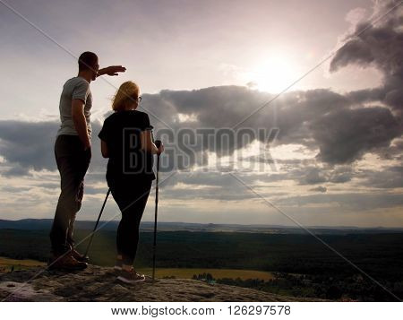 Couple Enjoying Marvellous Moments During Sunset . Young Pair Of Hikers On The Peak Of Rock Watch  T