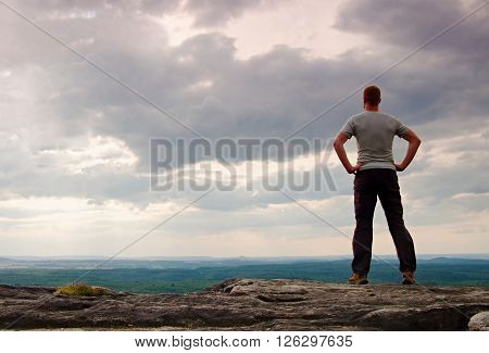 Gesture Of Triumph. Happy Hiker In Greyshirt And Dark Trousars. Tall Man On The Peak Of Sandstone Cl