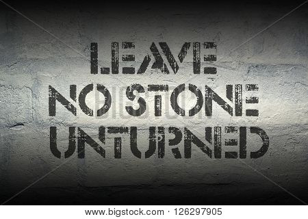 leave no stone unturned stencil print on the grunge white brick wall