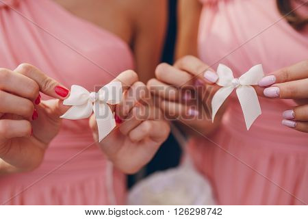 bridesmaid holding navesilli red bows in their hands