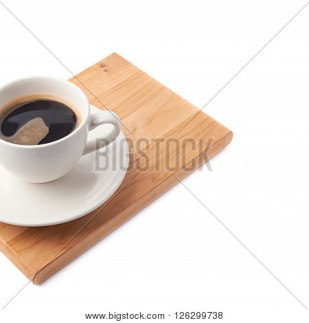 Fresh cup of coffee on a ceramic plate over the wooden serving board, composition isolated over the white background and framed as a close-up copyspace background composition