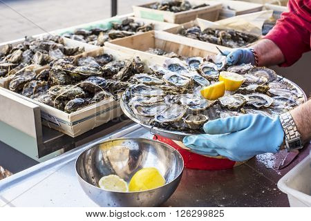 Tray of opened fresh oysters on half shell on ice with lemon in a street of Bordeaux capital of Aquitaine. France.