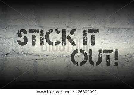 stick it out exclamation stencil print on the grunge white brick wall