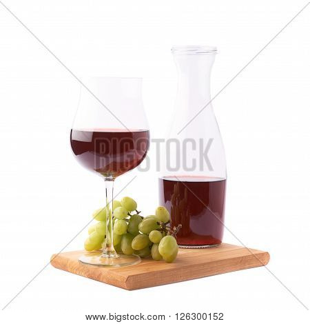 Glass of red wine next to a branch of white table grapes over the serving wooden board, composition isolated over the white background