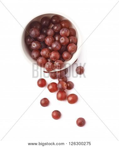 Dark red grapes spilled out of the white cermic bowl, composition isolated over the white background