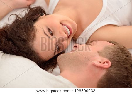 My darling. Content nice loving couple lying in bed and smiling while looking at each other