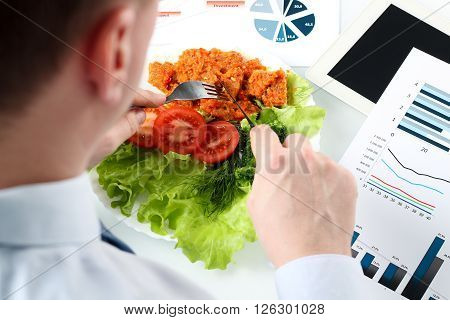 Close-up of businessman working on marketing strategy during business lunch.