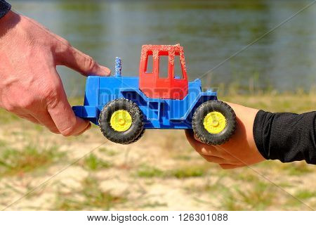 Father's Large Hand Pass Plastic Toy Truck To Hand Of A Little Boy. Hands In Blue And Black Shirts.