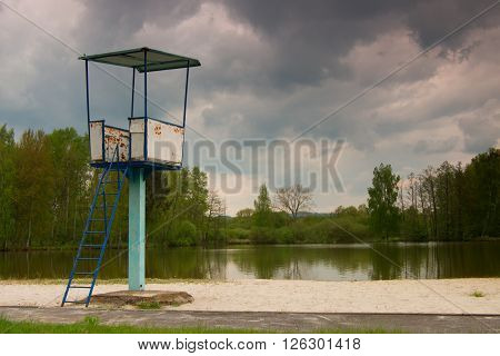 An Old White And Rusty Metal Lifeguard Tower With Chair On A Pond Beach