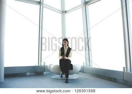 Japanese businesswoman is checking e-mail on cellular while sitting in modern office interior of skyscraper. Female traveler is using smart phone while is waiting for departure flight in airport hall