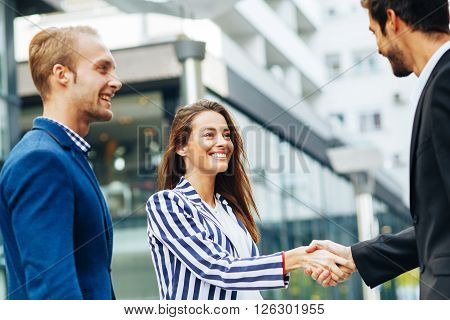 Business people handshake outdoor focus on woman face