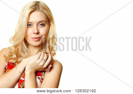 Attractive young woman smiles slyly on a white background