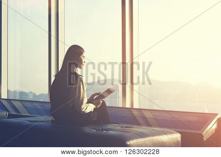Young Asian hipster girl is holding touch pad while is sitting in modern interior against window with city view. Businesswoman is waiting her fly in airport and thinking about her awaited vacations